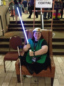 Sitting with legs tucked, RMN gear, & smock holding a lightsaber
