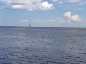 Lake Superior on a sunny day. A few puffy clouds, a boat in the blue-grey water