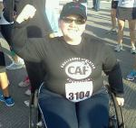 Pavement in background with a fat white woman sitting in a manual wheelchair with workout clothes, race number, and flexing one bicep