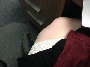 A picture of a pair of lace Undersummers peaking out from under a black skirt with a red cardigan visible. Photo is a body selfie with a pale fat leg visible