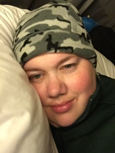 A pale person wearing a grey fleece camoflage hat and a dark sweatshirt with her head on a white pillow that curves from the front to the back of her